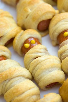 Spooky little mummies made from hot dogs wrapped in crescent rolls (a.k.a. pigs in a blanket dressed up for Halloween). Easy, fun treats for Halloween parties for kids or serve as appetizers for grown up parties.