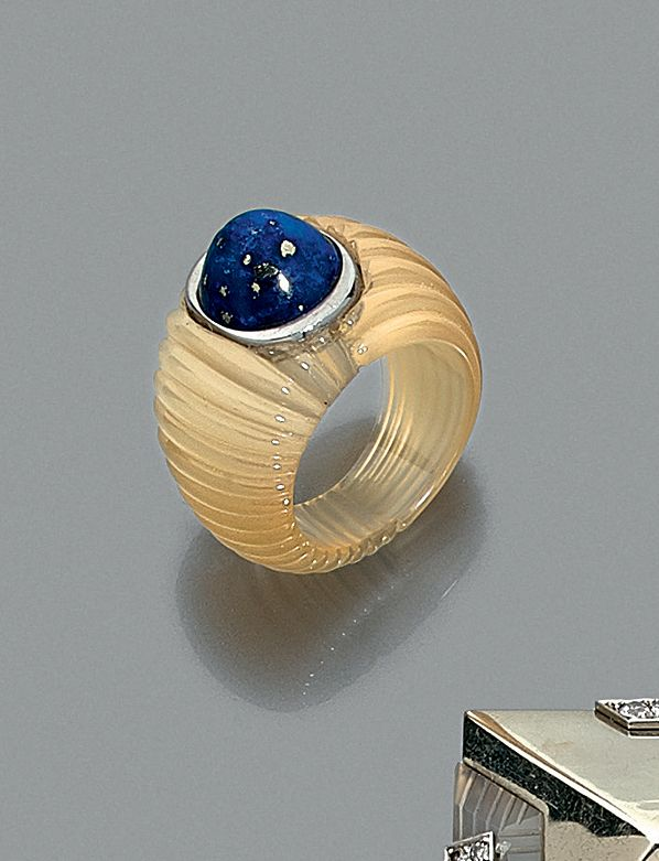 par Suzanne BELPERRON Rare BAGUE en agate blanche godronnée flanquée d'or gris (750 millièmes) serti d'un cabochon de lapis-lazuli.