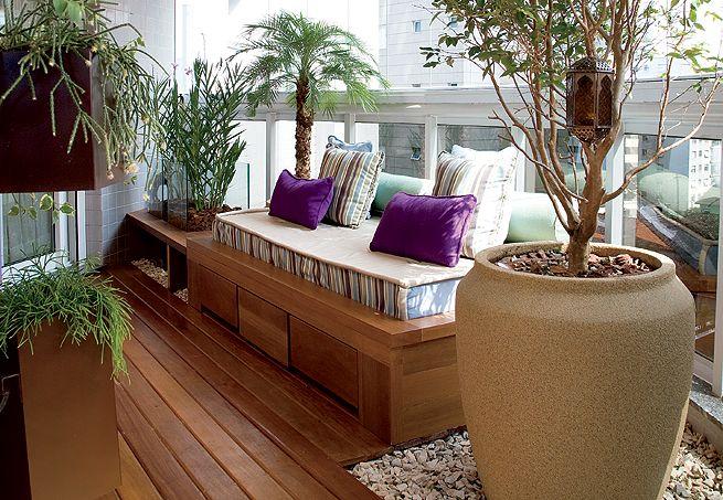 O banco de madeira maciça com futon complementa a sensação de aconchego da varanda, projetada por Drica Diogo, da Pateo Paisagismo