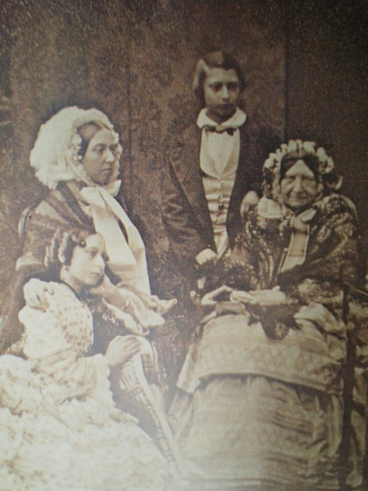 Queen Victoria in a frilly bonnet, posing with mother, Victoria, the Duchess of Kent , and children, Princess Alice and Prince Albert Edward.