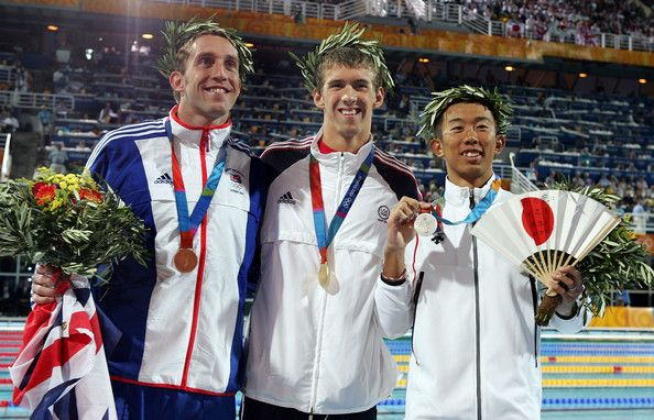 Michael Phelps Photos Photos - Gold medalist Michael Phelps of USA, silver medalist Takashi Yamamoto of Japan (R) and bronze medalist Stephen Parry of Great Britain (L) celebrate on the podium during the medal ceremony of the men's swimming 200 metre butterfly event on August 17, 2004 during the Athens 2004 Summer Olympic Games at the Main Pool of the Olympic Sports Complex Aquatic Centre in Athens, Greece. - Olympics Day 4 - Swimming