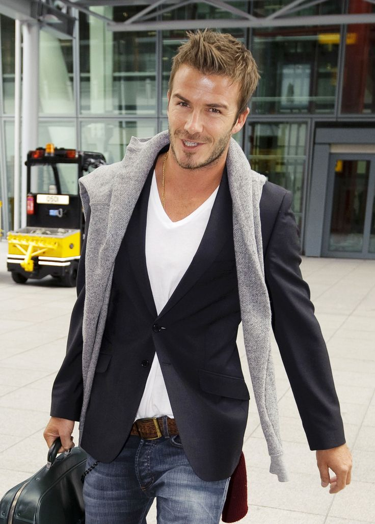 David Beckham flashed a smirk as he arrived at London's Heathrow Airport today without the supportive foot brace he's been wearing since tearing his Achilles tendon. His rehabilitation program allowed David to take time off from soccer to relax in LA