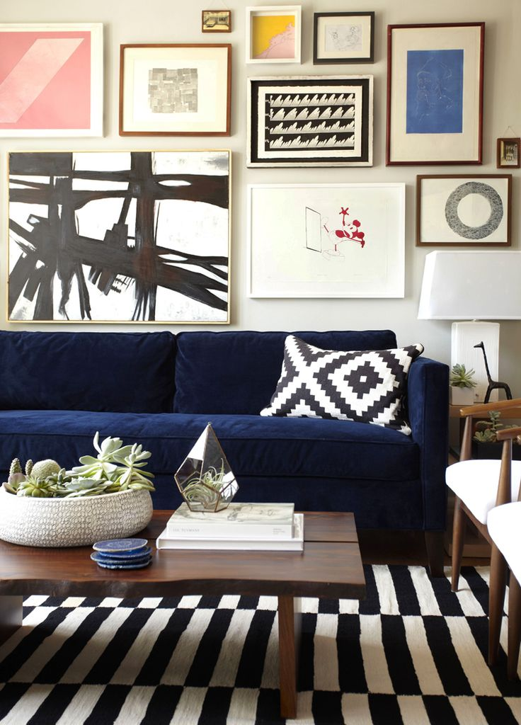 Orlando's Soria's art wall, shot by Zeke Ruelas, from Emily Henderson  Resources are West Elm unless specified otherwise: Rug from Ikea, $299, Dunham Sofa ($1499 in performance velvet ink blue), Abstract Art Piece ($179), Ombre Pillow ($34), Giraffe Accessory ($24)