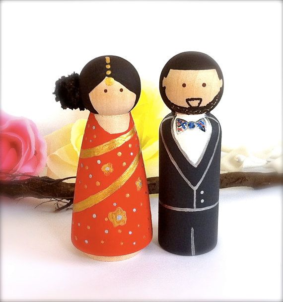 How adorable are these Indian cake toppers? The bride is dressed in traditional red and gold but take a look at her modern groom! Grooms have a choice, they can dress traditionally into an achkin (long decorated top with tighter pants), a suit, or tuxedo.  #Tacori  #YourBestFriendsWedding