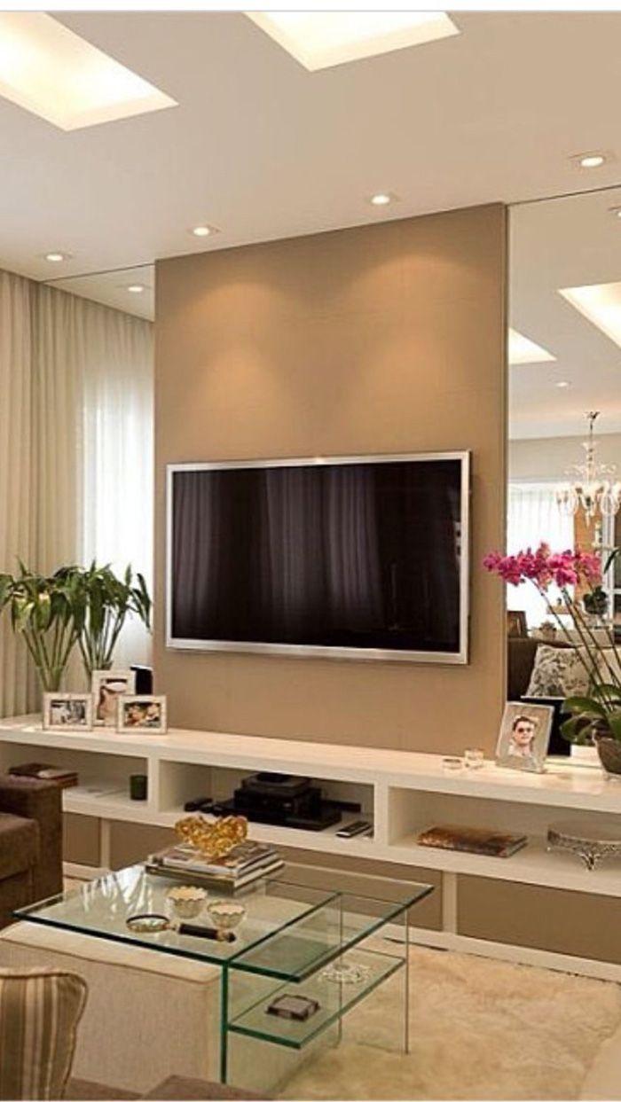 Esse lindo painel para TV com espelhos nas laterais é uma ótima inspiração para salas estreitas. O rack é laqueado com nichos e gavetões e é estreito, cerca de 35cm. O painel da TV pode ser feito de madeira com laminado liso (cor corda da Fórmica por exemplo) ou de gesso com pintura.