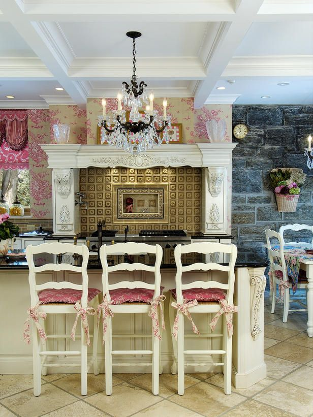 French Baroque style kitchen with intricate pink toile wallpaper, crystal chandelier, pink brocade cushions and window covering and ornate carvings.