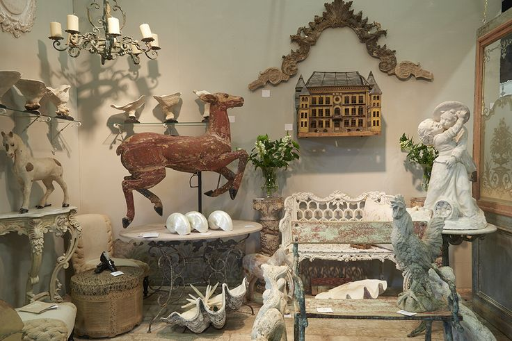 Antique garden seating, stone statuary and a fancy antique bird aviary in the form of a French chateau.