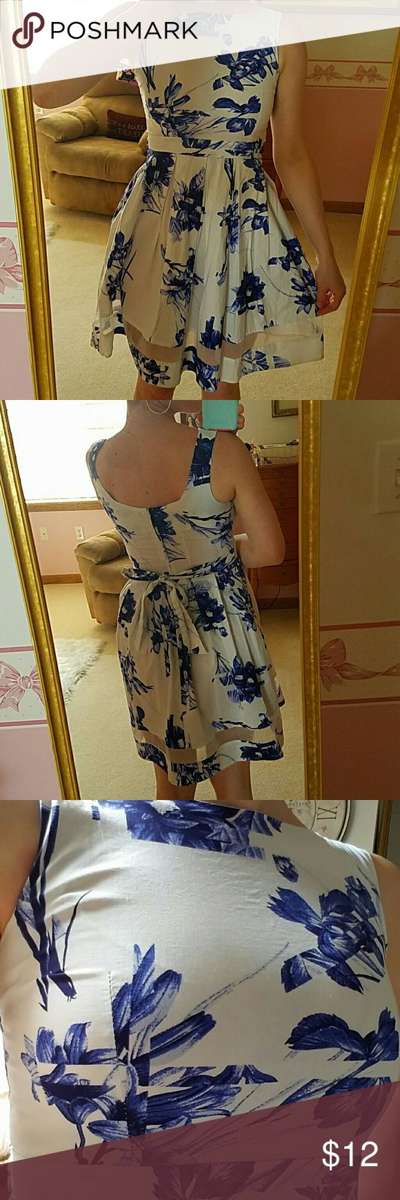 Floral Blue and White Dress Stunning tea dress! Zips in the back with a back tie. Cute, modern design of the see through hem line and gorgeous floral design, sure to be a head turner! Dresses