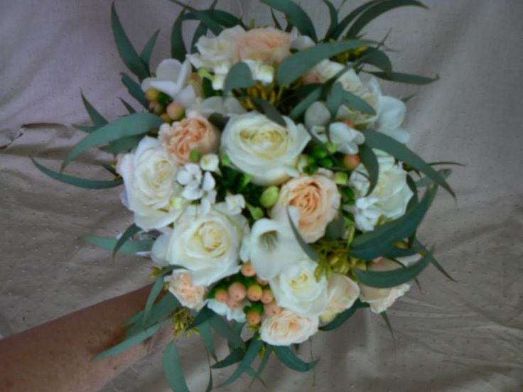 White & apricot roses with white freesias, apricot hypericum berries & white bouvardia surrounded with nutty gum foliage