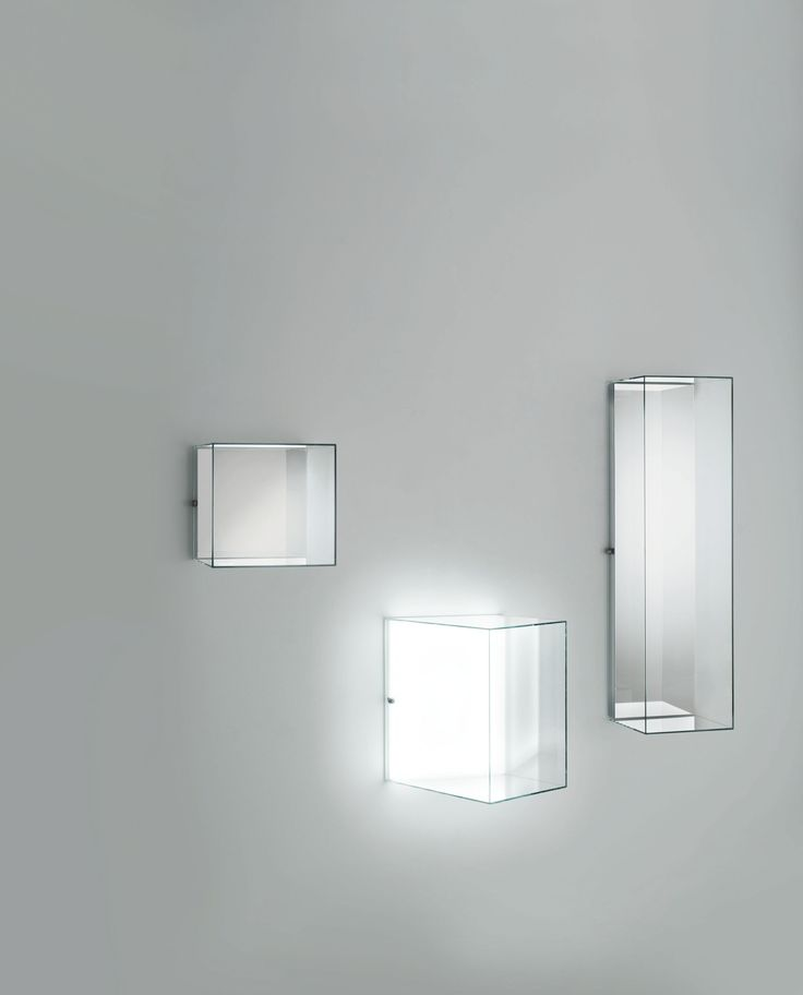 HEIGH-HO design Piero Lissoni | Aerial hanging display cases in transparent extralight or spy glass, available in straight and oblique versions and with a mirrored back or with illuminated Led system. Special hinges fixed to the wall allow the glass cases to revolve enabling access to the inside. In the version in spy glass with lighting system, when the light is off, the display look like pure mirror volumes. When the light is on the glass gains transparency revealing the objects inside.