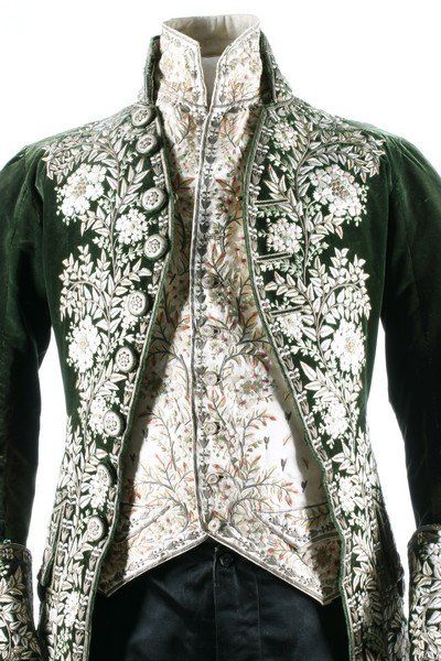 Detail front view, 3-piece court coat, France, c. 1790. Green velvet, heavily embellished with floss silk flowerheads and foliage; waistcoat: ivory silk satin with floral embroidery; black satin breeches.