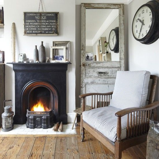 Rustic living room, farrow and ball cornforth white, wall hung black & white slate council notice, large black station clock, mirror made from salvage door, black iron victorian fire, old lantern, stripped waxed floorboards, milking stool, arm chair cushions grey/brown & white stripe