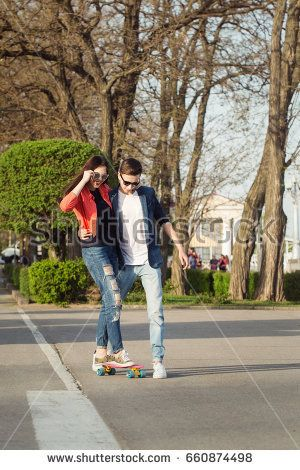 Enamored teenagers. The guy is teaching his girlfriend to skateboard. Date of hipsters.