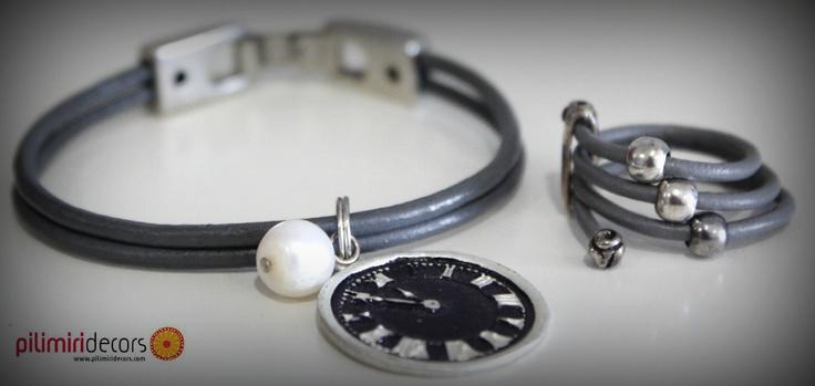 Pulsera de cuero gris como detalle lleva una perla y una fornitura con forma de reloj, esta pulsera es una combinación perfecta con este anillo de cuero y cuentas de plata