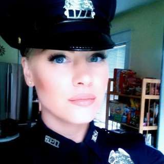 """Self portrait in uniform by Elizabeth Rooney, a police officer in Boston US. Officer Rooney is making  a point about what """"dress like a woman"""" means (visit Article for more context)."""