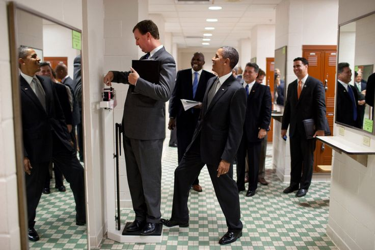August. 9, 2010: President Barack Obama puts his toe on the scale as Trip Director Marvin Nicholson tries to weigh himself during a hold in the volleyball locker room at the University of Texas. By Pete Souza.