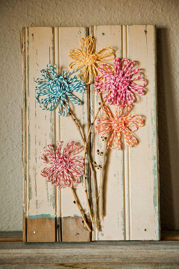 lente decoratie: een oude plank, wat twijgen en wol tussen spijkertjes.