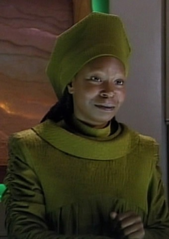"""Guinan had """"some dealings"""" with Q sometime during the 22nd century and indeed other members of the Q Continuum, some of whom she said """"were almost respectable."""" Her exact relationship with Q remains unclear, though it was evidently hostile. Q described Guinan as an """"imp"""" and stated: """"where she goes, trouble always follows."""" Guinan raised her hands, implying she had some sort of ability to defend herself from Q's powers."""