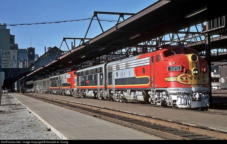 ATSF 325 Atchison, Topeka & Santa Fe (ATSF) EMD F7(A) at Chicago, Illinois by Kenneth A. Young. Chicago's Dearborn Street Station was the oldest of six large downtown passenger depots. Opened on May 8, 1885, it was closed by Amtrak on May 2, 1971. On the eve of Amtrak's startup, Santa Fe 325 is ready for a late afternoon departure.