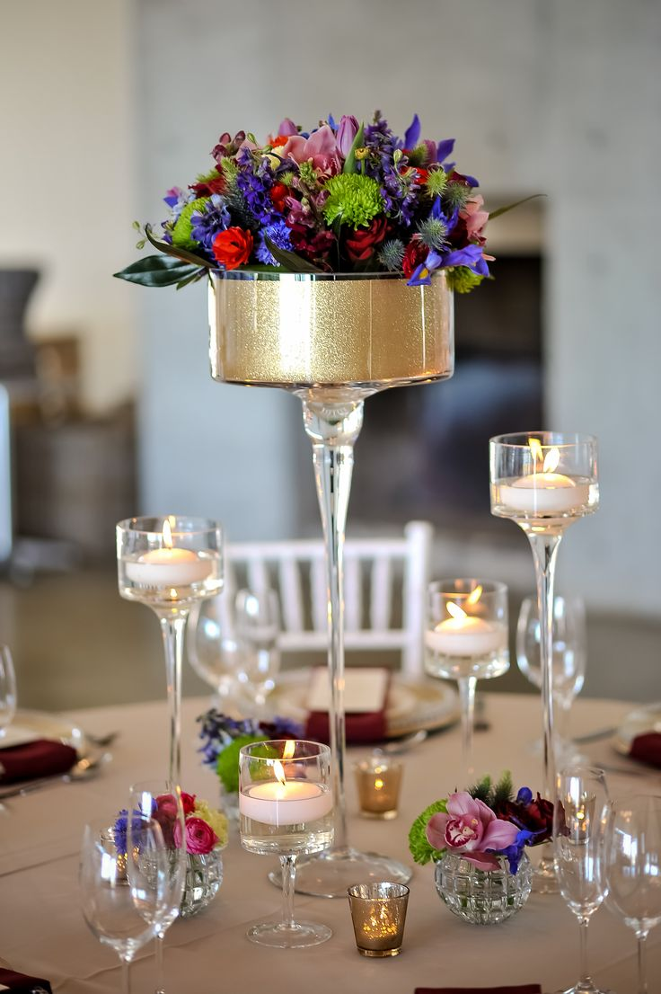 Tall stemmed holder with colourful flower arrangements and floating candles.