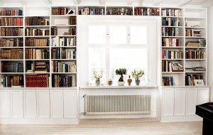 Platsbyggd bokhylla kring fönster.