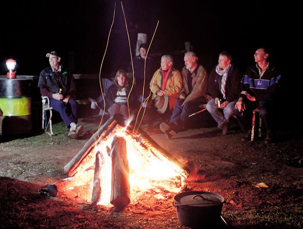 Friends and guests enjoy entertainment around the camp fire on the Farmstay Tour from Sydney