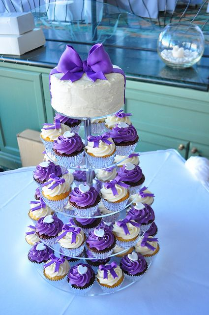I think I'd prefer a cute cake topper over the big bow, maybe just a crisscross of purple ribbon. Purple cupcakes and small cake.