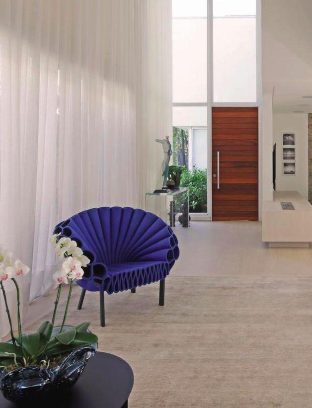 O simples abrir e fechar de portas de correr integra e delimita os espaços de uma das casas do condomínio Bauhaus. Hall de entrada (ao fundo), estar e um aconchegante home theater compõem a ala social