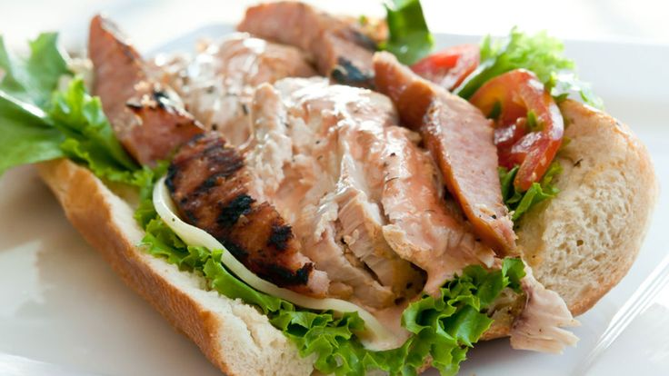 """The """"Conquistador."""" Thick pieces of juicy, well-seasoned and baked chicken breast -- packed into a toasted French roll (smeared with house-made special sauce) with leaves of crisp Romaine, slices of juicy Beefsteak tomato and sharp Provolone."""