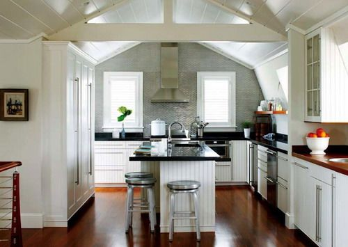 Gorgeous cottage kitchen with sloped ceilings, white beadboard kitchen cabinets with black granite countertops, sink in kitchen island, stainless steel ideas