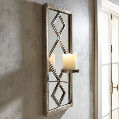 With a touch of Hollywood glam, our champagne-colored sconce lights up any room. Wrought iron diamond shapes are overlaid on a wood-framed mirror, which captures the flickering light of a pillar candle surrounded by glass. It will make a stylish statement in your entryway or dining room, or try two sconces flanking a doorway or window.