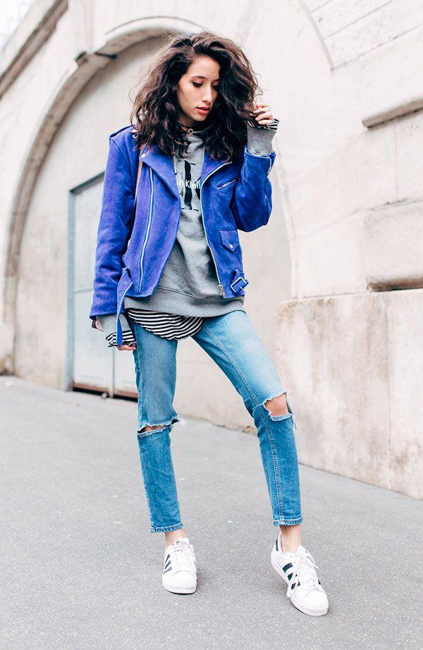 Street style look com jaqueta de couro azul, moletom cinza, calça rasgada, blusa listras e tênis branco.