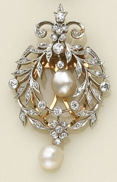 A diamond, pearl and platinum-topped gold clip-brooch the foliate wreath design clip brooch with floral and fleur-de-lys accents, set throughout with old European-cut diamonds, suspending two baroque pearls. Edwardian or Edwardian style.