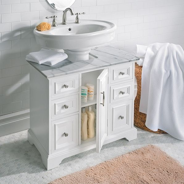 A Pedestal Sink Cabinet With Marble Top And Brushed Nickel