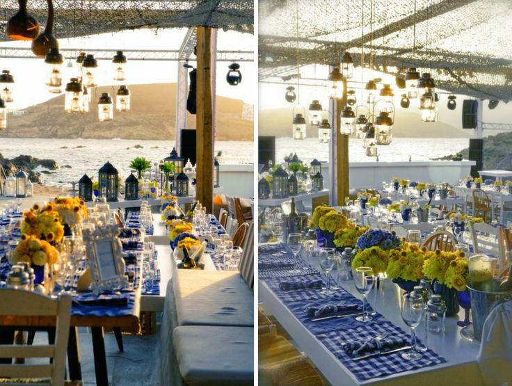 When Brazil Meets Greece Wedding @ Alemagou, Mykonos by De Plan V. Alemagou's dinner area, art de la table, long tables, hanging lanterns, sea view, sands of Ftelia beach, Brazilian and mediterranean culture comes together harmoniously!