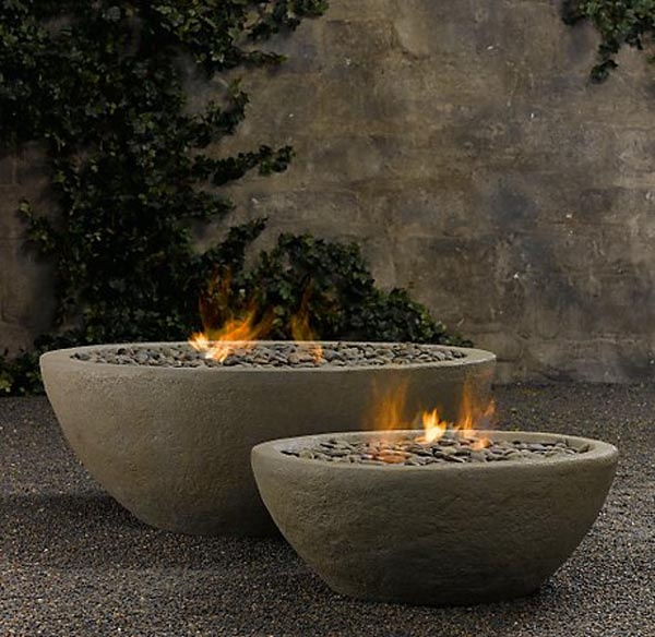 Lava Rock Fire Bowl is cast from high-quality concrete, shown here as a pair set on pea gravel in an outdoor room.  More info: Restoration Hardware site.