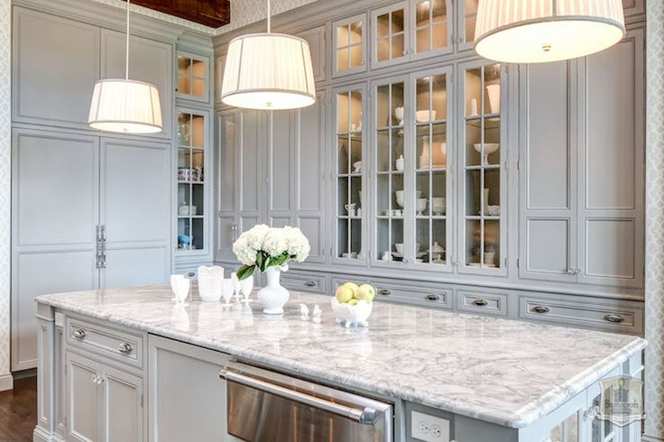 Traditional style kitchen features wall to wall gray built-in cabinetry framing glass front china cabinets adorned with brushed nickel hardware. A gray cabinet front two door fridge stands adjacent to the built-in cabinets across from a gray kitchen island fitted with under counter refrigerator drawer finished with a gray and white quartzite countertop illuminated by a trio of ivory pleated drum shade pendants.