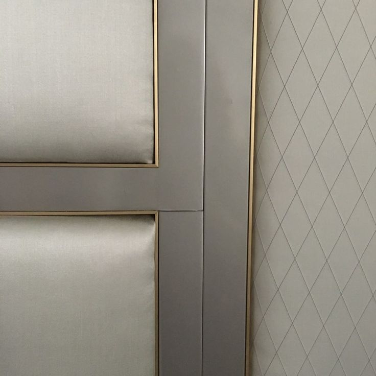 A padded headboard with inset bronze detailing