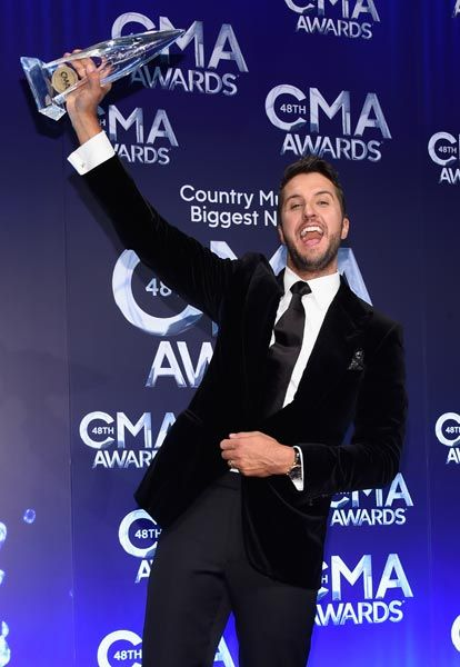 Luke Bryan proudly holds his entertainer of the year award at the 48th annual CMA Awards.