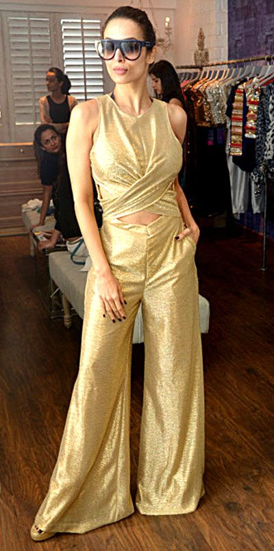 Malaika Arora Khan tries on a golden jumpsuit, while sister Amrita Arora Ladak looks on at Seema Khan's Christmas collection launch. #Bollywood #Fashion #Style #Beauty
