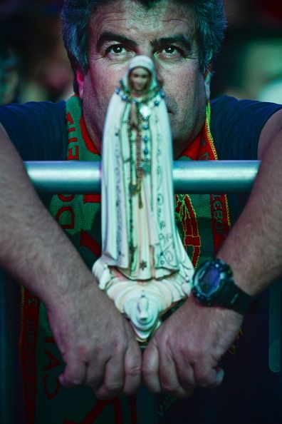 #EURO2016 A Portugal football team supporter holds an effigy of Our Lady Fatima as he watches the Euro 2016 semifinal football match Portugal vs Wales played...
