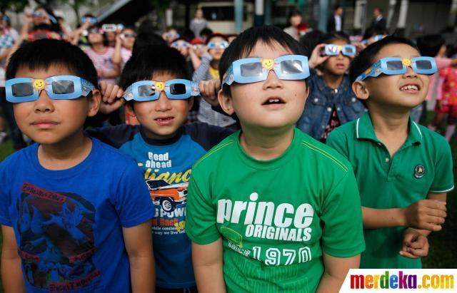 Anak-anak tampak mengamati fenomena gerhana matahari menggunakan kaca mata hitam di kota Tokyo, Jepang, Senin (21/5).