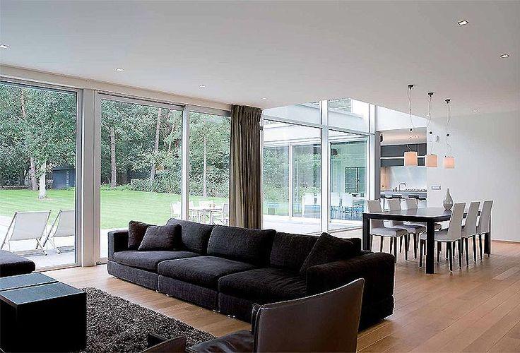 Schellen Architecten: Nijlen.  Interieur living met eetkamer op de achtergrond. Veel lichtinval door de grote ramen en uitzicht op de tuin en terras.