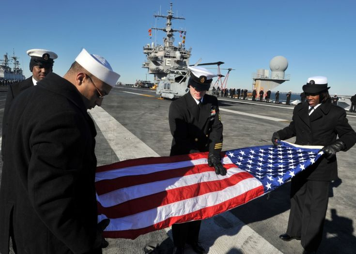 NORFOLK (Jan. 13, 2011) Sailors assigned to the aircraft carrier USS Enterprise (CVN 65) fold the national ensign as the aircraft carrier departs Naval Station Norfolk. Enterprise is deployed as part of the Enterprise Carrier Strike Group supporting maritime security operations and theater security cooperation efforts in the U.S. 5th and 6th Fleet areas of responsibility. (U.S. Navy photo by Mass Communication Specialist Seaman Jared M. King/Released)