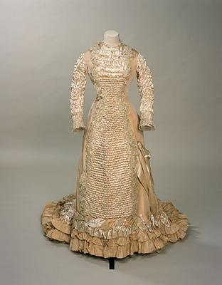 Ruched cream silk satin wedding dress, English, 1881. Worn with a wreath of orange blossom with wax flowers and myrtle.