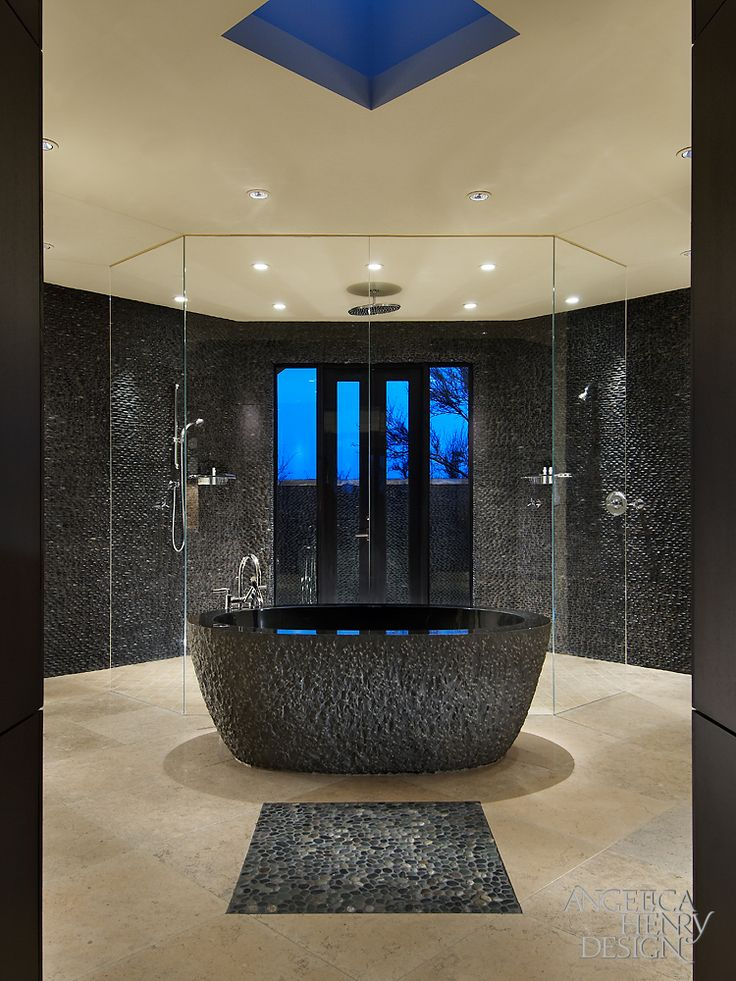 The textured black soaking tub takes center stage in this bathroom, with a pebble tile in front. Dual glass shower enclosures sit behind the tub.