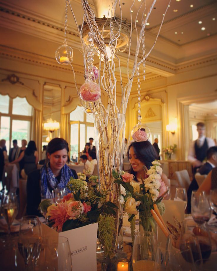 Wedding centerpieces: Crystal baubles hanging from branches and flowers at base of vase.