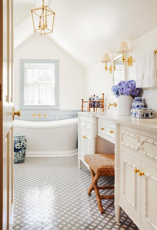 Gorgeous cottage bathroom boasts a seagrass x-stool placed on black and white lattice floor tiles at a white bamboo dual washstand accented with gold knobs and a white quartz countertop.