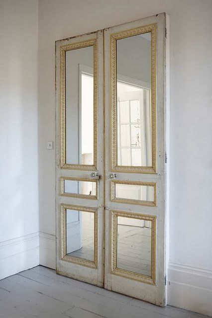 Pair of old doors with mirror inserts against a plain wall or on closet. Love this idea for our bedroom!