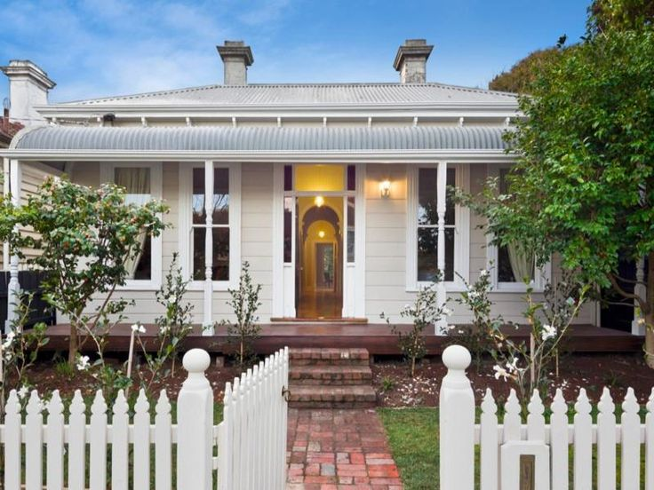 Roofline; bullnose verandah roof; symmetrical facade; double windows; cream weatherboard with white trim.
